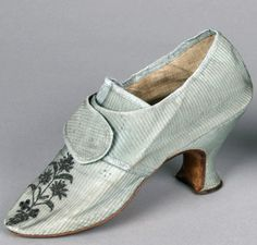 Buckle shoes, England, 1775-1785, Of turnshoe construction with blunt oval toes and covered thin louis heels. Shoes consist of grey blue ribbed silk uppers with silver embroidered floral motif on vamp, medium high tongue, square toe, round straps to buckle over vamp, one of which is pierced and a straight side seam. Uppers lined in natural leather and the insole is brown leather. Heels covered in matching grey blue ribbed silk are white stitched in the channel. Sole is of sueded brown…