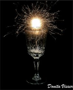 The effects of the sparkler really makes thia champagne glass stand out.