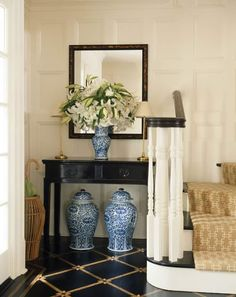 Entryway with blue and white porcelain ginger jars and beautiful paneling combined with traditional flooring. Very nice small entry. This is from her Southampton Porfolio.