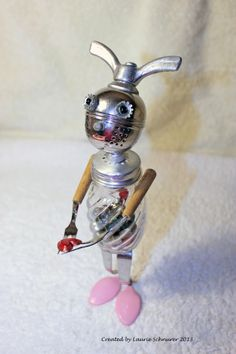 """I give my heart to you."" Original junk art created by me (Laurie Schnurer) in 2013. The salt shaker can be opened to exchange the ""guts"" with whatever you'd like. Also the head piece turns so he can have bunny ears or a mohawk."
