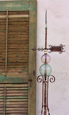 """""""Antique iron lightning rod with copper finial and antique amethyst and green glass globes. I love how the colors in the lightening rod mimic the colors in the old shutter."""""""