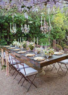 Grande table en extérieur avec chandeliers suspendus pour soirée romantique dans le jardin