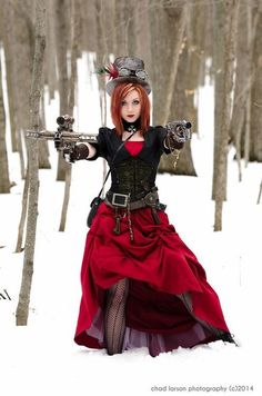 Steampunk Vampire Hunter with weapons, in the woods in the snow. Red dress, stockings, corset, top hat, goggles, crucifix, gun, crossbow, wooden stakes - Winter Steampunk scene - For costume tutorials, clothing guide, fashion inspiration photo gallery, calendar of Steampunk events, & more, visit SteampunkFashionGuide.com