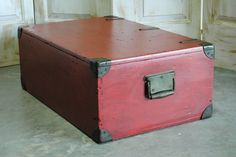 Military trunk originally used to store field radio equipment. Packing diagram for radio still intact on inside lid. Painted red and finished with a walnut stain. Great conversation piece that can be used for a coffee table and/or storage.