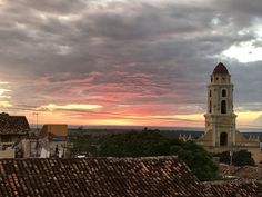 A sweet #sunset in Trinidad #Cuba - Not pictured the canchánchara in my other hade made with rum, honey, and lime. Get the recipe, great #cubatravel stories, and #traveltips in my latest book #CubicletoCuba. #books #travel