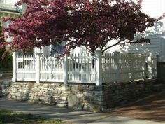 A New Wall that Looks Old. Natural stone topped with a wooden fence.