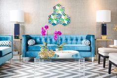 modern minimal style living room with blue velvet sofa, taupe textured wallpaper, chevron black and white floors