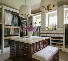 Custom walk-in closet features a wall of clothes rails over stacked pull-out pant rails adjacent to window wall framed by built-in cabinets and pull-out drawers across from a dark stained closet island with marble top and drop down bench illuminated by a pair of brass drum pendants.