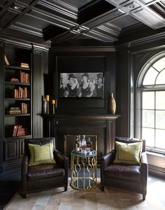 Dark wood paneling, HD Buttercup leather chairs, and a hide rug by RH give the…