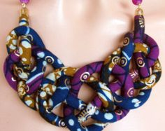 This gorgeous necklace is made out of two tubes of fabric that I sewed and fitted around synthetic wool; cotton handmade batik and wax print with golden print. Perfect colors for your winter holiday celebrations. I have added a josephine knot from my past macrame experience.Sits beautifuly on the neck.  .Length from one end to the other in a straight line is 22.4 inches or 57 cm long .I have also added 3 inches of extention chain. Please let me know if you want changes on the length.  All…