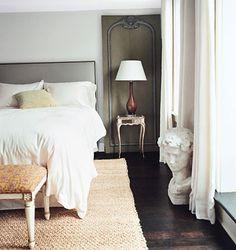 Master bedroom:: pale grey walls, grey headboard, natural flooring, white bedding