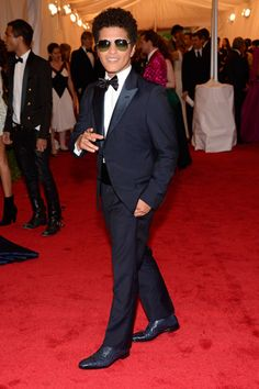 Bruno Mars entertained guests with a performance at the Costume Institute Gala at the Met, looking every bit the rock star in cool shades and a Prada tux.