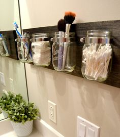 Mason jars attached to a wooden board make a farmhouse-chic bathroom storage option that keeps items off the vanity top. Perfect for holding cotton balls, Q-tips, makeup brushes, and toothbrushes and toothpaste, the jars attach to the board with hose clamps from the plumbing supply aisle. Get the tutorial at the DIY Playbook.  - Redbook.com