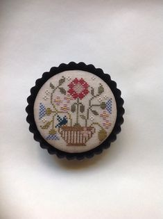 Cross stitched floral piece mounted in tart pan. Brenda Gervsis Design. Home Decor.