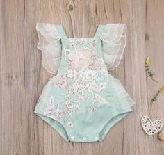 Eloise Green & Pink Vintage Embroidered Floral Birthday Tutu Romper This beautiful seafoam green tutu romper showcases delicate embroidered detailing through the bodice with a blush floral motif 3D design. Ruffled gauze detailing along the shoulders, sides, and bum creates the sweetest ruffle bum romper. Great for a first birthday shoot, or a summer soiree! For your one-stop Birthday Shop, make sure to check out our matching Birthday decorations.