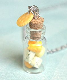 This necklace features a miniature bottle adorned with handmade cheese slices sculpted from polymer clay. The bottle pendant measures 2 cm tall and is securely attached to a silver tone chain necklace