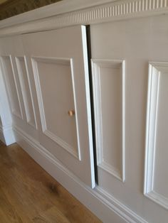 Secret cupboard built into beaded wall panelling with fancy detailing