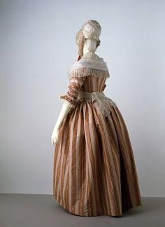 In the 1770s a new style of wearing gowns was introduced, called a polonaise. Using buttons and loops, the skirt of the gown was draped up to create a swathed effect at the back. Also introduced during this decade were a range of striped fabrics, often in a complex arrangement of colours with both sharp and shaded edges, as seen in this example. Other new developments were the ruched sleeve cuffs and bodices that meet in the centre, eliminating the need for a stomacher. This dress is shown…
