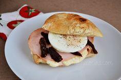Sándwich con huevo pochado, pechuga de pavo, queso y tomate deshidratado