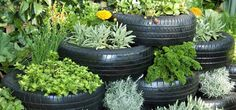 Here's a super cool idea for a larger garden space. Using your customized tire planters, stack them up to create your own garden retaining wall. Not only is this beautiful to look at, but this feature is easy to maintain. Once you water the top part of your retaining wall, the water will seep down the structure to ensure all your plants will be watered. Stack the tires as high or low as your like.
