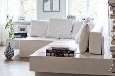 Mathias e Julie, relaxados, mostram o interior e nós perguntamos: mesmo com uma criança, o sofá é branco? Sim! O reino da pequena família preza pela estética e é muito bem decorado. A sala de estar uniu soluções práticas e elegantes: o grande sofá branco inspira conforto e é regulável por meio de módulos, se transformando em cama, mesa de centro ou em um grande banco.