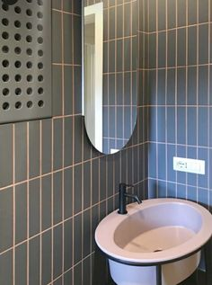 RM\Architecture - bathroom cladding made with porcelain tiles from the Lingotti collection by Tonalite and pink colored grout that matches the color of the washbasin