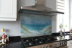 This bespoke piece of fused glass artwork is a panel that went to a home in Halifax, West Yorkshire. It's a splashback which depicts a beautifully soft beach scene, with washed out, dreamy colours that give the glass a very serene mood. The customers wanted the piece to give that feeling of discovering a beach and stepping out to see the sea for the first time, bringing a little joy from the outdoors inside.