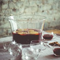 Spice Island Punch: pomegranate juice, blood orange juice, dark rum, cognac, dry curaçao, allspice dram, small orange, cinnamon sticks