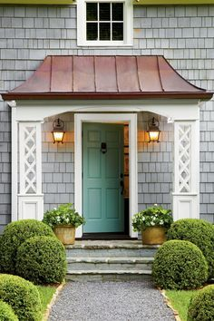 A swooped copper roof and bluestone stoop add prominence to the cottage's entrance. White lattice columns and a front door with a punch of color put a subtle twist on tradition.     Classic cottage essentials: Front door paint, Quarry (23-26) prattandlambert.com