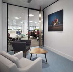 Meeting Rooms >> Retro Office Furnishing >> We love the simple but cool design of this #meetingroom. The retro style wood table and wood framed chair, next to a more modern grey armchair, create a more homely feel to this #smallmeetingspace. The #officewallart  of an Incredibles-film inspired #superhero and dog brings a light touch of humour to this not-so-corporate #officespace. See more of this #officedesign and meeting room ideas on our website - just click the image...