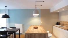 Un îlot central coloris chêne naturel sépare la pièce en deux espaces.