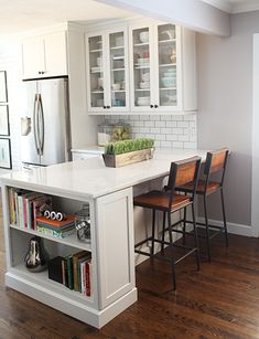 LOVE this peninsula with the bookshelf, and the glass door cabinets and subway tile. Also really like the look of the fridge encasement. Great wall color too. jb Bower Power- Ashleys kitchen