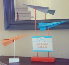 homemade stands and paper airplanes... cheaper than painted wooden airplanes?