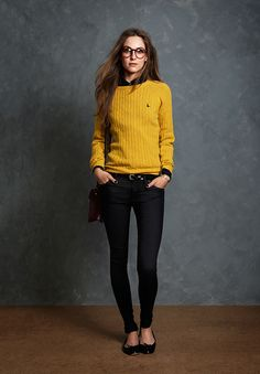 Bright yellow cable knit sweater over black button-up shirt, black skinny jeans, black ballet flats, black belt