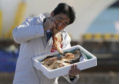 Japan's Prime Minister Shinzo Abe, who is also leader of the ruling Liberal Democratic Party (LDP), eats a local grilled fish during his official campaign kick-off for the December 14 lower house election, at the Soma Haragama fishing port in Soma, Fukushima prefecture, December 2, 2014. (REUTERS/Issei Kato)