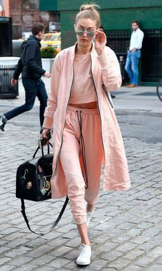 11 April Gigi Hadid was spotted out and about in New York wearing a blush pink tracksuit with a matching coat. - HarpersBAZAAR.co.uk