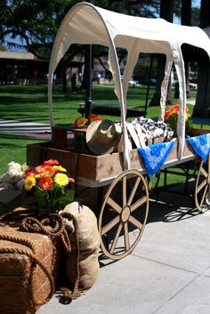 Photo 1 of western theme - used a long folding table with cardboard wheels, hula-hoop wagon braces with material as cover. If sturdier wheels, beneath would make a great reading area, and the upper part could house books and other resources. Rodeo Party, Cowgirl Party, Cowboy Birthday Party, Cowboy Theme, Western Theme, Pirate Party, Country Western Parties, Fundraiser Party, Wild West Party