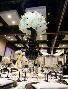 White anemones and hydrangeas in a towering black vase. This centerpiece make a elegant statement for any event decor..