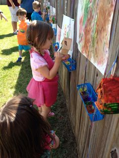 Kids' art party.  Pin paper to a fence with pushpins, hang a tray with cups of paint and let them paint!  No easels needed!