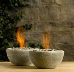 The flaming rock bowls pictured above are actually a product that Restoration Hardware used to sell. Although they're no longer available, knowing RH, I'm sure they weren't cheap. Enter ManMade, who got all fancy with the concrete and made a DIY concrete fire pit for about $40 in supplies:  Concrete mix Mixing bowls for the mold Non-stick cooking spray Large bucket for mixing and masonry trowel Gel fireplace fuel canisters  Replacement grill grate  Fire safe decorative stones  As for the…