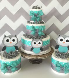 This Set of 3 Owl Baby Shower Diaper Cakes would make the perfect display at the upcoming themed party!  Owl Diaper Cake Set includes: 3 Tier Diaper Cake measuring 10 inches wide by 14 inches tall and includes 40-45 Pampers Swaddlers Diapers in size 1 (2) Matching Mini Diaper Cakes Quality Ribbons and Bows Gray Paper Shred