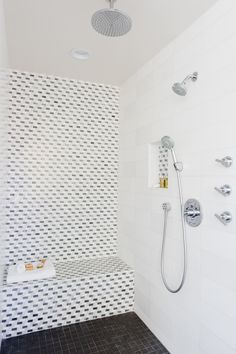 an angled seamless glass shower is clad in large gray marble staggered tiles on ceiling and wall accented with three shower heads alon