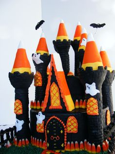 """Halloween Candy Corn Castle Cake - Halloween Candy Corn Castle Cake  6""""x 4"""" round on top of a 10"""" by 4"""" round  Dark chocolate butter cake and Almond Rum cake (colored orange) with vanilla butter cream icing. Everything is covered in chocolate or vanilla fondant with a brick pattern. Bats, ghosts are fondant. Bats are on floral wire. Almost a whole bag of Brach's Candy Corns, Reese's Pieces and Hershey's Candy Corn Kisses  'glued' on with royal icing and or butter cream icing. Licorice fence…"""