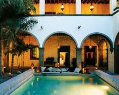 The poolside patio of a Mexican hacienda is lit with copper lanterns. The hanging tin star lights are a traditional design.