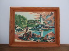 Vintage Framed Lighthouse Paint By Number by jessamyjay on Etsy. This lovely coastal scene depicts a rocky shoreline with a row boat in the foreground and a beautiful lighthouse in the distance. This colorful paint by number painting is held in a wooden frame with string across the back, ready to hang!
