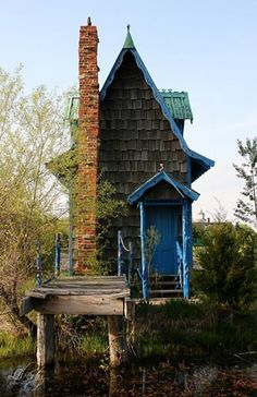 "reachable only by a drawbridge, the whimsical ""Mother-In-Law House"" sits in the middle of a lake just off Route 66 in Missouri; photo by Jen / Liberty Images"