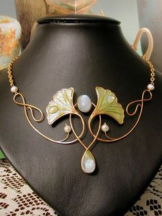 Gilded wire necklace, with a ginkgo leaves motif, rendered with polymer clay framed by wire; the small dew drops are moonstones cabochons, such as the central upper and lower stones. Set with freshwater pearls.