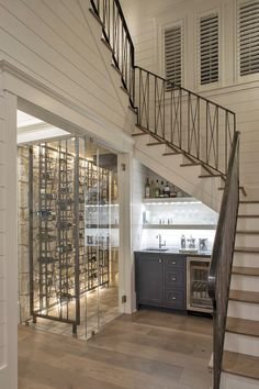 A glass wine cellar is located beside black wet bar cabinets fitted with a glass front beverage fridge mounted beneath a lighted stacked white floating shelves positioned against white shiplap cabinets and above a small sink. Under Stairs Wine Cellar, Bar Under Stairs, Kitchen Under Stairs, Glass Wine Cellar, Home Wine Cellars, Beer Cellar, Stair Shelves, Stair Storage, Wine Storage