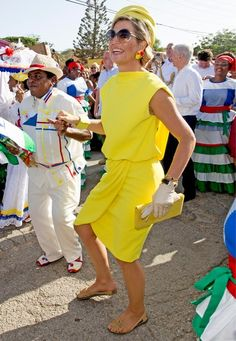 Fashion-Looks: Dancing Queen! Ausgelassen feiert Königin Máxima auf Bonaire in der Karibik den Día di Rincon. Nicht nur im zitronengelben Dress mit passendem Hut ist sie während des Festivals der schillerndste Blickfang.