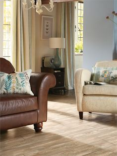 A cosy living room with contrasting armchairs and Pine Fimis laminate flooring.